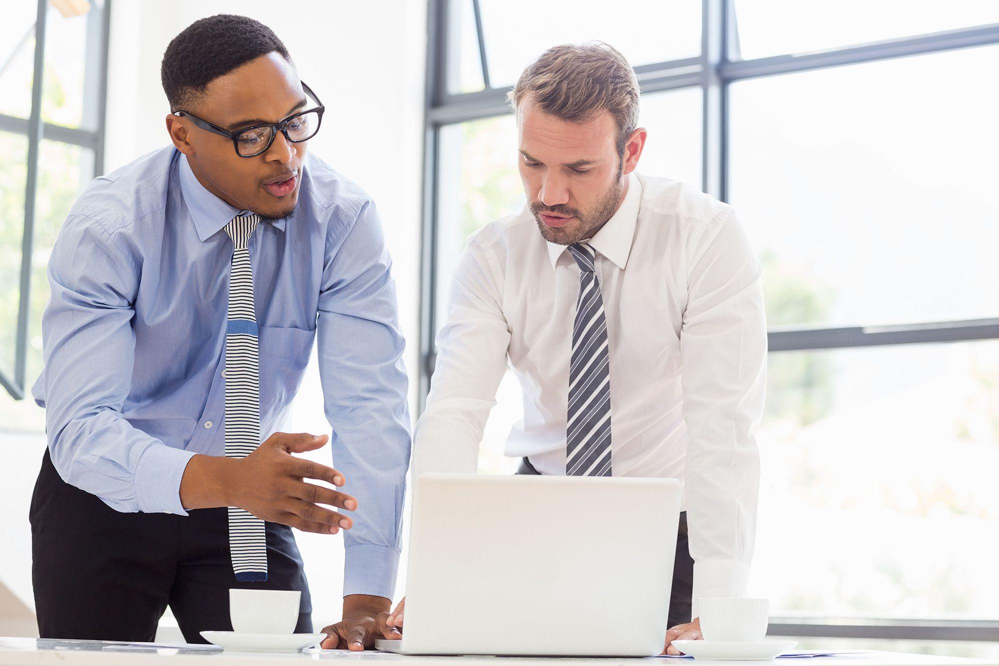 dois homens conversando e utilizando notebook