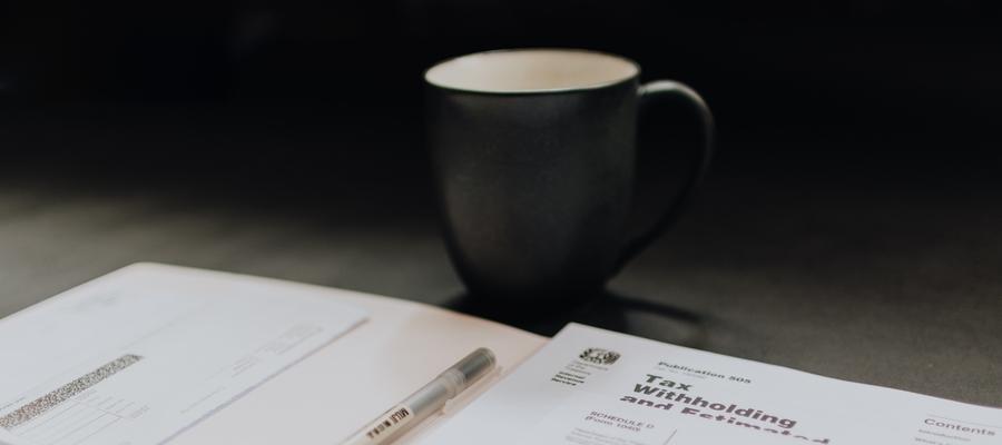 Documentos e xicara de cafe sobre a mesa