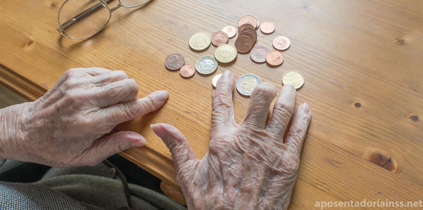 Mãos idosas contando moedas na mesa
