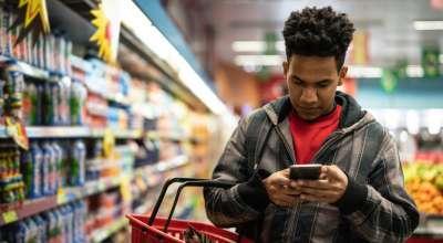 Consumidor no supermercado com ceular